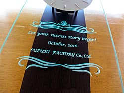 「Let your success story begin、日付、会社名」を前面ガラスに彫刻した、開業祝い用の掛け時計