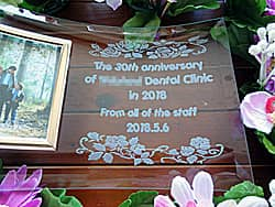 「The 30th anniversary of ○○ dental clinic」「From all of the staff」「日付」「バラの花の飾り」を彫刻した写真立て(歯科医院の周年祝い用)