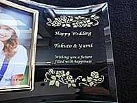 「Happy wedding、新郎と新婦の名前、Wishing you a furure filled with happiness」を彫刻した、結婚祝い用のガラス製フォトフレーム